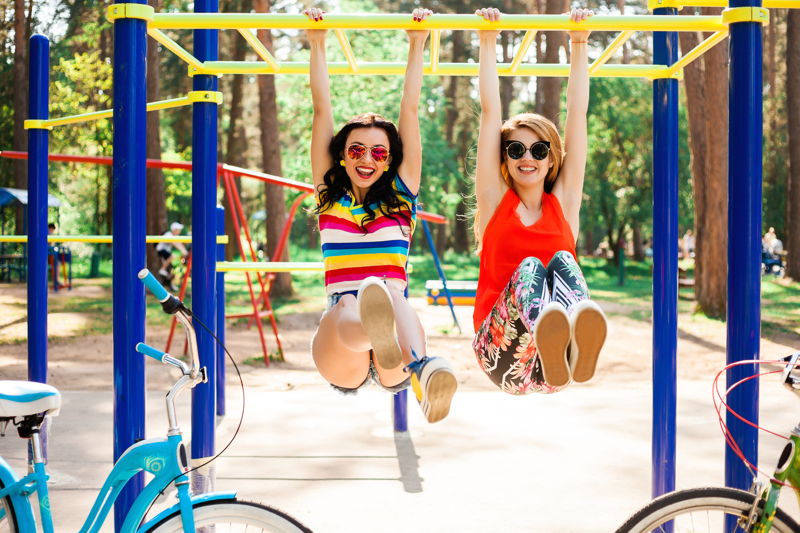 Two beautiful happy funny hipster girls, teenagers, best friends are hanging on the crossbar on the horizontal bar on the playground, laughing, crazy emotions, blonde and brunette, bright clothes